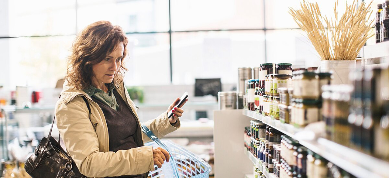 woman holding smart phone while shopping in supermarket