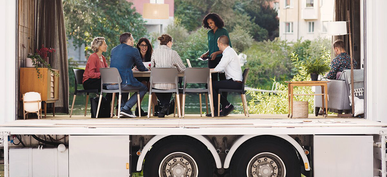 business collegues discussing in portable office truck at park in the city